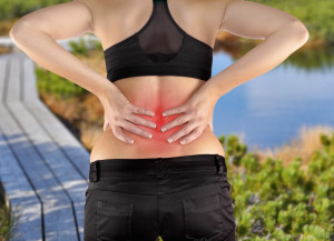 Back pain. Athletic woman in black sportswear standing and rubbing the muscles of her lower back, cropped torso portrait.Autumn Park Backgroun